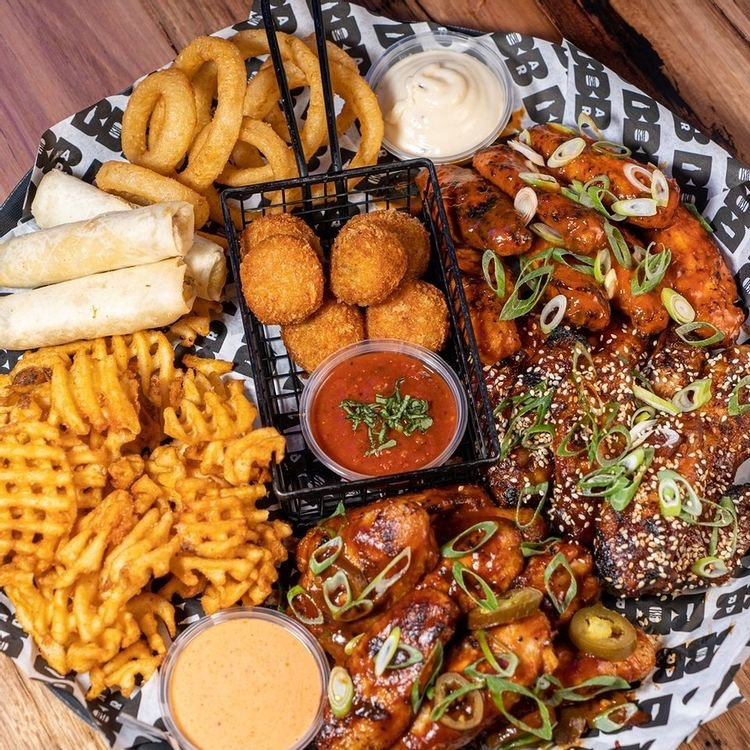 Tray of chicken wings waffle fries and tasty sides