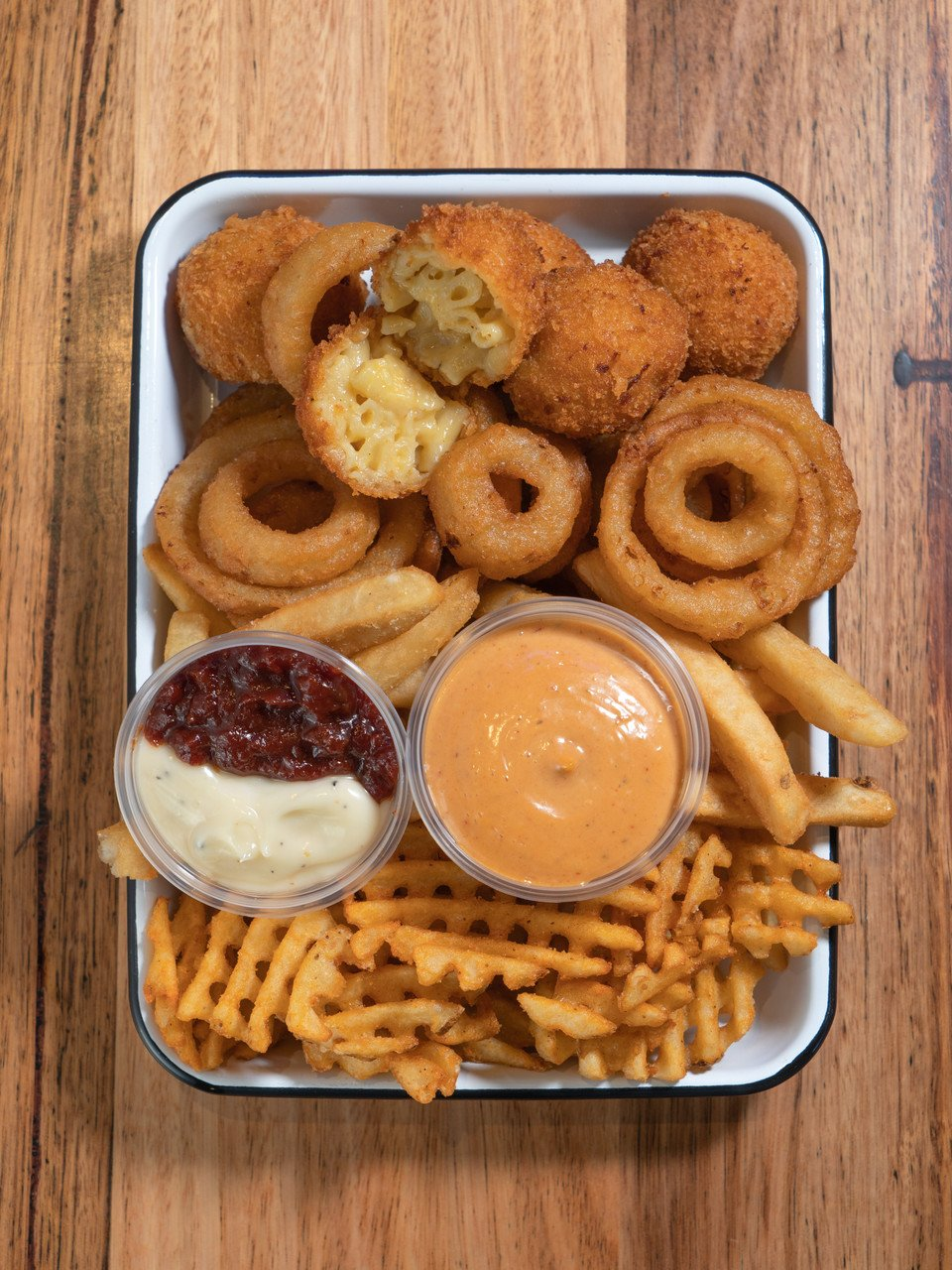 Tray of delicious sides waffle fries onion rings and mac n cheese balls